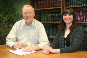 Mayor Chuck Burtcher signs the Child Abuse Prevention Month proclamation with Amanda Fortney.