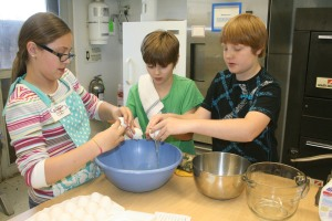 Members of the FCC Cook Team prepare to break six eggs for a cake mix.
