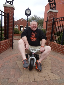 "Price Purvis, President of Guthrie Kiwanis Club, tries out a scooter in advance of the ""Big Wheels"" race, scheduled for Friday, April 19th at 5PM at Harrison and 1st St. in downtown Guthrie."