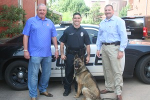 Max Fairchild (left), Officer Jacob Garrett, Police Chief Damon Devereaux and Jalo stand outside the Guthrie Police Department.