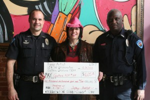 """The Tipsy Artist, Tiffany Bohrer, donates to the Shopping with a Cop. Officers Jason Hamilton (left) and Jonathan """"JW"""" Williams accept the donation."""