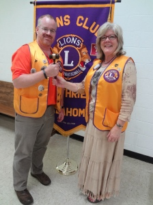 Incoming Lion President  John Wood accepts the leadership gavel from Outgoing Lion President Cheryl Tarter as the leadership of the Guthrie Noon Lions Club transitions at a recent Installation of Officers Meeting.