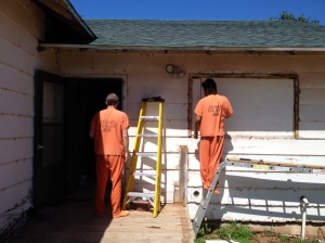 Two county trustee inmates work on the outside of the lake house as part of the renovation of the home.