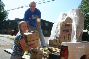 Spoonful Pharmacy's Phillip Carothers hands Central Elementary Principal Dani Watson with a box of school supplies.