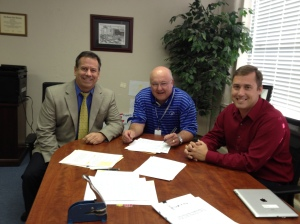 Financial Advisor Jon Wolff (L), Supt. Dr. Mike Simpson and School Board President Travis Sallee sign the final documents to set up a bond election for Nov. 4.