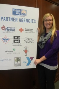 Natalie Hardin, new United Way of Logan County Coordinator, displays a poster showing all 10 Partner Agencies.