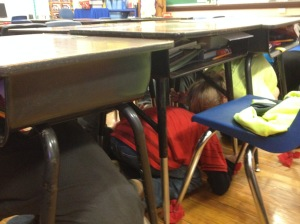 Student go through an earthquake drill by going underneath their desk and waiting for about 60 seconds.