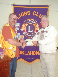 Lion President John Wood presents a check for $1,000 to Richard Hendricks, Director of Territorial Capital Sports Museum.