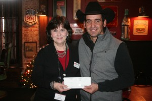 Robert Simpson with the Lazy E Ranch and Arena donates a check to Karen Wallis with the American Red Cross.
