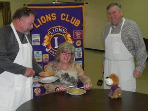 """Clay Tarter (L) and Richard Ireton  (r)  prepare to serve a sampling of pancakes to Cheryl Tarter in preparation for the """"Pancake Feast"""" held Friday, March 27th at the American Legion Building for both lunch and supper"""