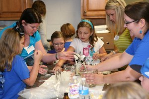 A crew of children and adults make bars of soap and lip gloss that were taken to the Maudie Hirshie Shelter.